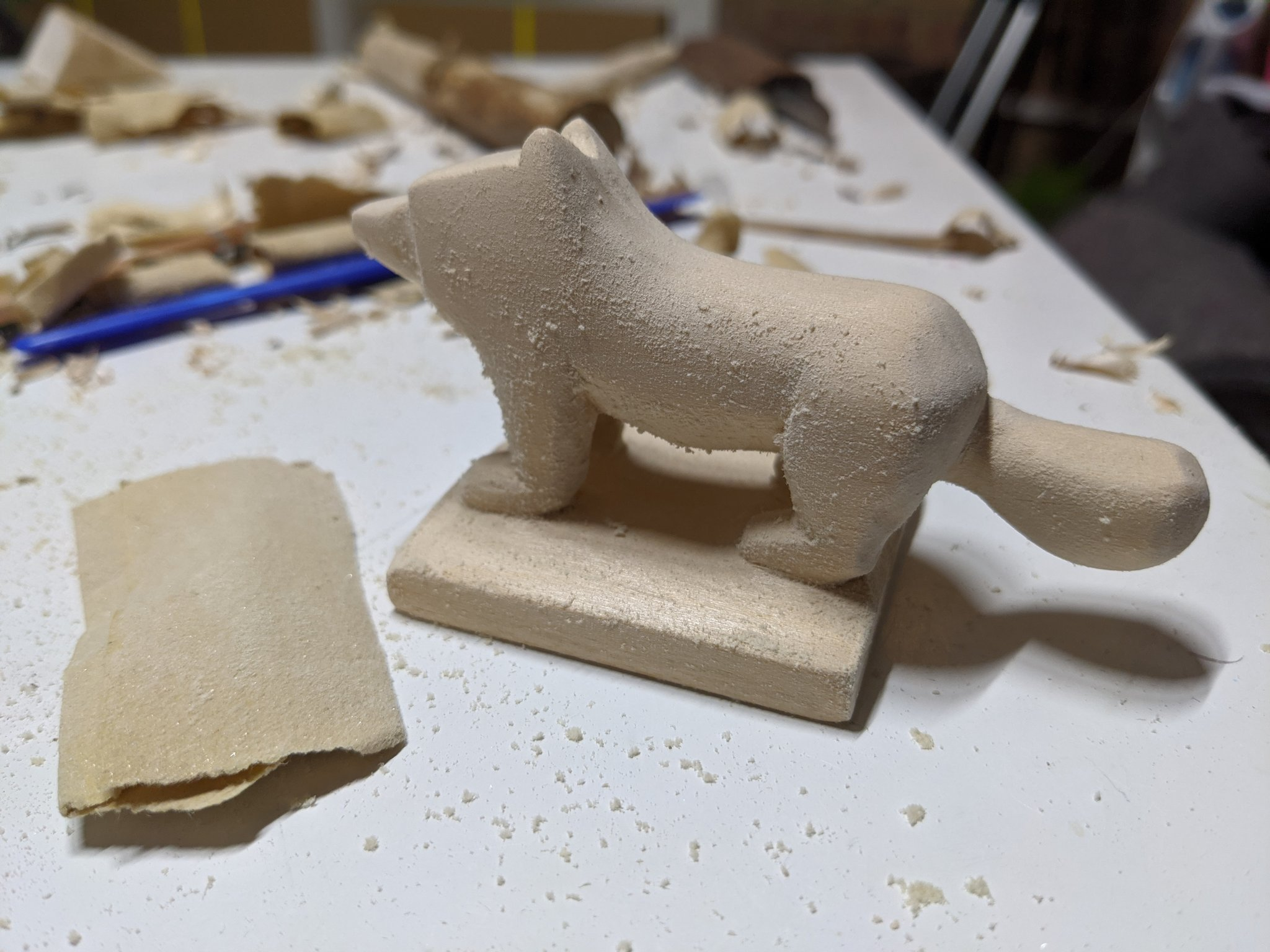 Sandpaper next to the dog, with the dog covered in a soft fluff like appearance after being sanded